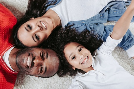 Top view portrait of parents and daughter relaxing on the warm carpet at home. They are looking at camera and laughing