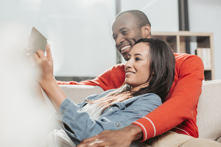Happy family enjoying weekend together indoors. They are looking at tablet and smiling Stock Photo