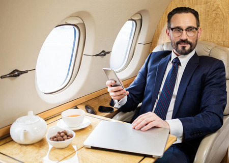 Waist up portrait of glad elegant male in modish suite relaxing in airplane seat with cellphone in hand, his notebook is lying on table Foto de archivo