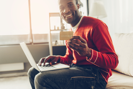 Smiling guy sitting indoors and showing gold card. Laptop is standing on his knees. Online shopping concept