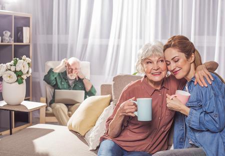 若い女性を抱きしめる幸せな祖母の肖像画。彼らは飲み物のマグカップを味わう。ファミリーコンセプト