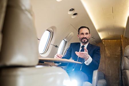 Angolo basso del passeggero allegro dell'aeroplano che si rilassa nel suo sedile alla tavola del vassoio e che sorride mentre parlando con qualcuno
