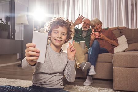 Portrait of cheerful curly boy taking selfie with grandmother and grandpa. They tasting cup of tea on sofa. Entertainment concept Standard-Bild - 95276759