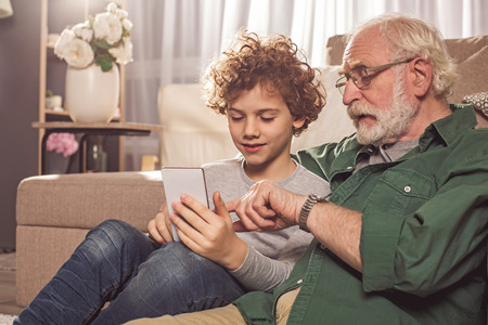 Attentive granddad pointing finger in mobile. Smiling boy keeping it in hand. Communication and technology concept Stock Photo