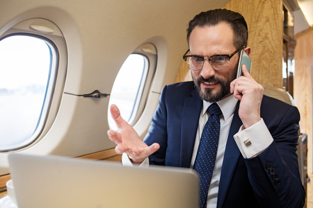 Things go worse. Portrait of dissatisfied diplomat in private airplane talking by mobile phone and looking at laptop screen, he is gesticulating expressing his irritation Banco de Imagens