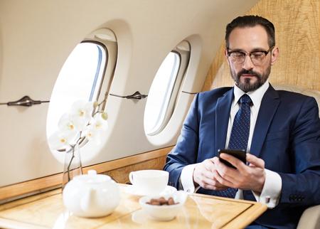 飛行機で旅行する静かな中年男性のウエストアップポートレート。彼は座っている間、携帯電話でメッセージを送っている 写真素材