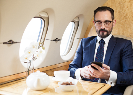 Waist up portrait of tranquil middle aged man travelling by plane. He is texting message on mobile phone while sitting Stockfoto