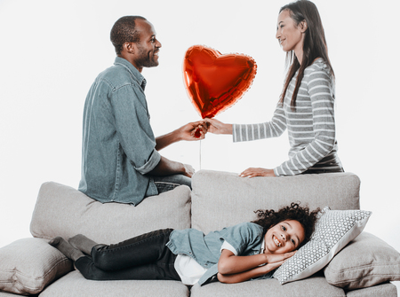 Pleased kid reposing on comfortable sofa, her father giving toy heart to mother and smiling. Isolated on background Stock Photo