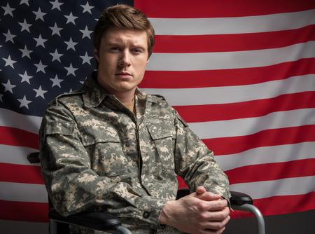 ハードな表情でカメラを見て、深刻な障害のある軍人のウエストアップ肖像画。彼は手を錠に組み込んで車椅子に座っている。背景に米国フラグ 写真素材