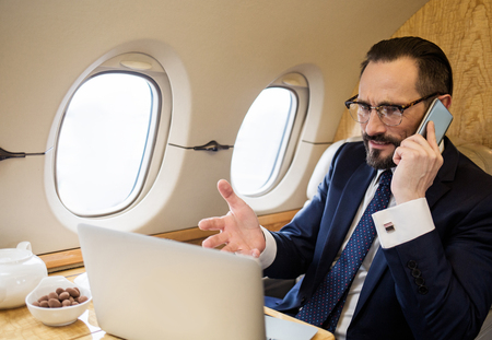 Displeased businessman in aircraft talking by phone and looking at notebook screen