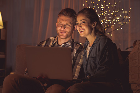 Portrait of beaming female and cheerful male watching at notebook computer in apartment. Leisure concept Foto de archivo - 95277017