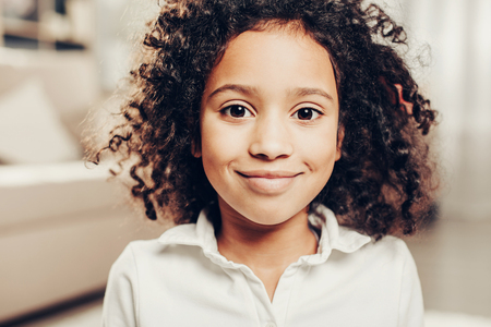 Portrait of cheerful african child with curly hair looking at camera with delight. Focus on girl Banque d'images