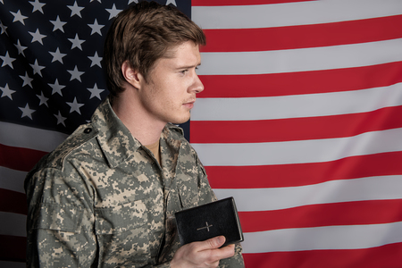 Tranquil young military man standing and holding the Bible in his hand with serene look. USA Flag on background. Copy space in right side Stock Photo