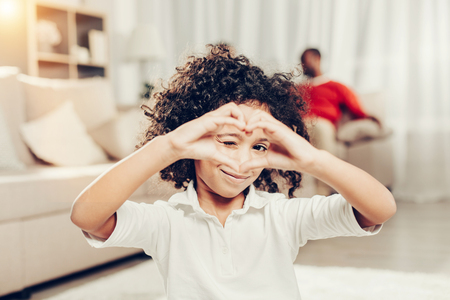 Portrait of little glad kid looking through fingers showing love sign while sitting indoors. Focus on girl. Parents on background
