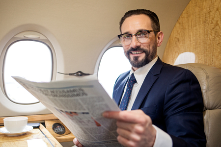 Portrait of pleased bearded male sitting in airplane seat and holding paper, he is looking at camera with joy