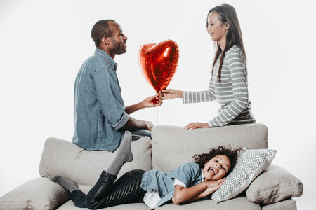 Content little girl resting on divan while enjoyed mom and dad handing each other air heart with love. Isolated on background