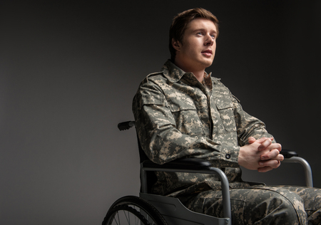 Cheerful disabled young military man looking up with hope. He is sitting in wheelchair with his hands folded in the lock. Isolated on grey background. Copy space in left side