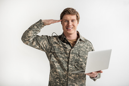 Happy male soldier saluting while having electronic device in hand. He is looking at camera and smiling. Isolated on background