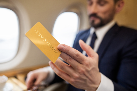Wealthy businessman sitting in airplane and holding gold card in hand. Focus on card Stock Photo