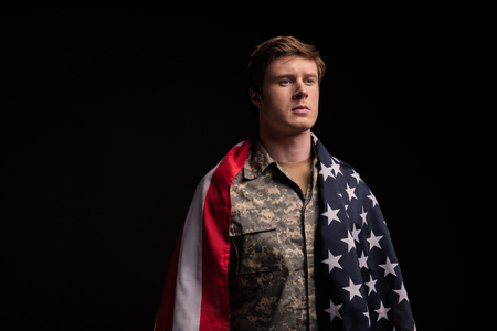 Waist up portrait of serious male soldier standing covered in usa flag. He is looking with sadness. Isolated on background. Copy space in left side