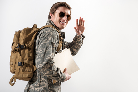 Cheerful military guy waving his hand and smiling. He is looking at camera while going away. Isolated on background. Copy space in right side