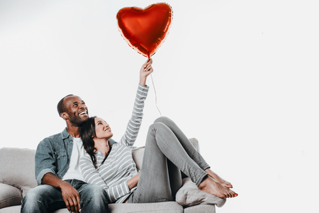 Pair of passionate people spending time on couch with joy. Female leaning against male and holding up toy heart. Copy space in right side. Isolated on background