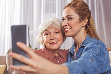 Portrait of smiling grandmother and happy daughter creating photo by mobile. Family concept 版權商用圖片