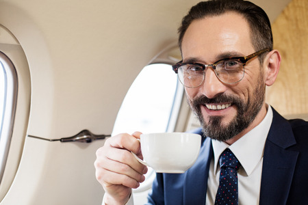 Portrait of joyful businessman in airplane cabin holding cup of tea and looking at camera with smile Stock Photo