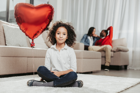 Home comfort. Portrait of calm girl sitting on carpet at home with air balloon in shape of heart while parents sitting on couch. Focus on kid Stock Photo