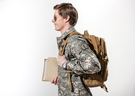 Happy male soldier going somewhere. He is smiling and holding document case in hand. Young guy wearing rucksack and spectacles. Isolated on background Фото со стока