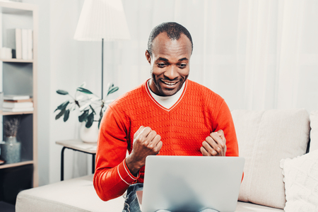 Portrait of content african guy rejoicing while sitting with gadget in comfortable living room