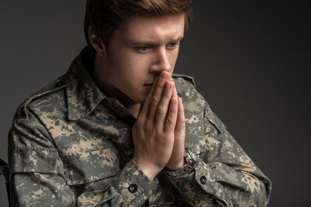 Despondent young military man praying. He is looking down with frustrated look. Isolated on grey background