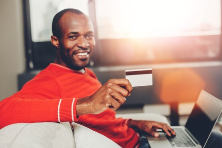 Portrait of pleased african man making purchase by internet while resting with notebook indoors. Focus hand holding credit card Stock Photo - 95277461