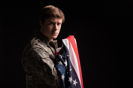 Unhappy male american soldier looking at camera and holding flag in hands with sad look. Isolated on background. Copy space in right side