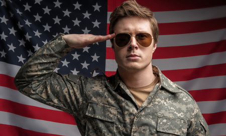 Portrait of sedate soldier standing on background of the usa flag. He is returning a salute with his right hand. Concept of pride