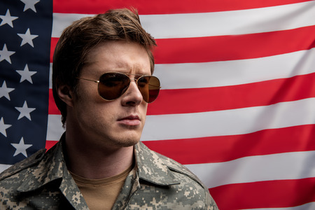 portrait of sedate soldier standing on background of the usa flag with serious look. He is wearing eyeglasses and military uniform