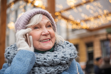 Portrait of happy senior woman talking on mobile phone and smiling. She is standing on street and smiling. Winter holidays concept Stock Photo