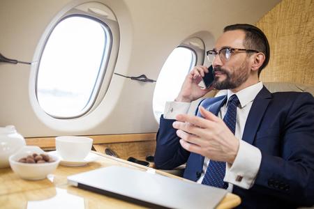 Homme d'affaires solide tranquille assis dans un siège d'avion de première classe, il parle par téléphone portable et gesticule Banque d'images - 95277658