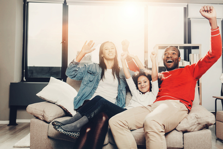 Portrait of joyful mother, father and kid sitting on sofa and rejoicing. They are raising their hands. Copy space in left side