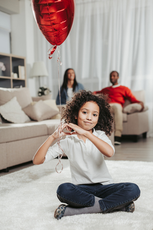 I love my parents. Portrait of smiling child resting on rug in apartment and showing love gesture. Mother and father are behind. Focus on girl Stock Photo