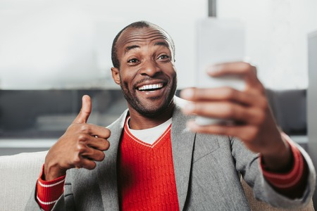 Portrait of enjoyed african guy gesturing and laughing while speaking online. Communication concept Stock Photo