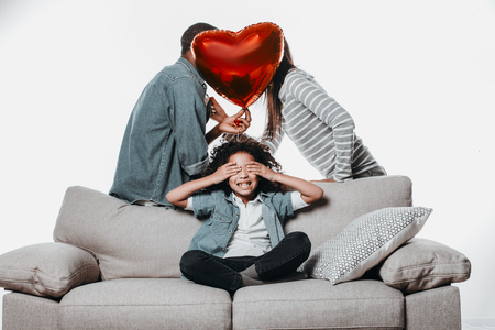 Young parents putting out of sight her faces with air heart and their content daughter sitting and hiding eyeballs behind palms. Isolated on background Stock Photo