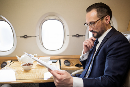 Serene handsome man reading newspaper while sitting in comfortable airplane seat at tray table