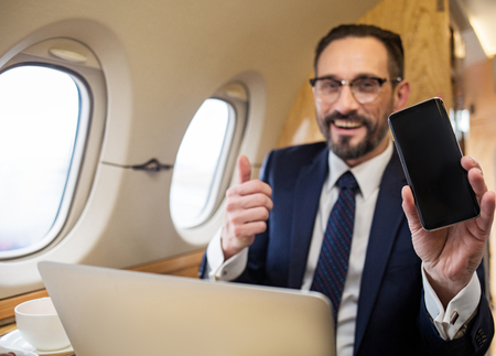 Portrait of smiling businessman showing mobile phone and holding his thumb up. Focus on device
