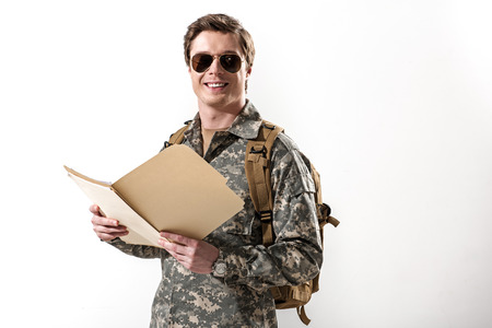 Cheerful young soldier looking at camera and smiling. He is holding opened folder and wearing rucksack and spectacles. Isolated on background. Copy space in right side