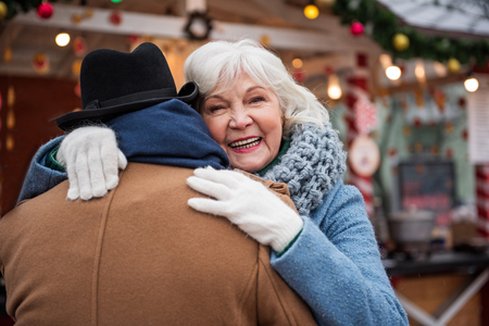 Portrait of happy old woman hugging her husband with love. She is looking at camera and laughing. Focus on male back