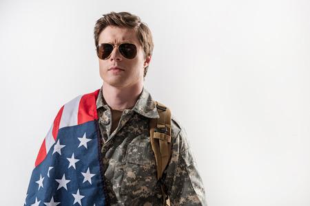 彼の肩に私の旗を持っている深刻な軍人のウエストアップ肖像画。彼はリュックサックを持って眼鏡をかけている。背景に隔離されています。右側