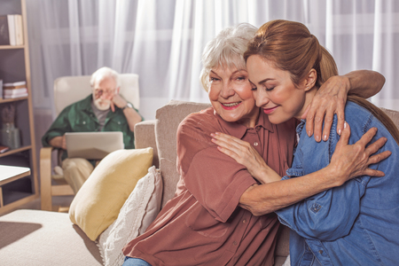 Outgoing granny embracing cheerful adult daughter while sitting on sofa. Granddad typing in laptop. Domesticity concept Stock Photo