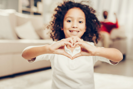 Waist up portrait of happy african girl demonstrating heart with her fingers. Focus on hands