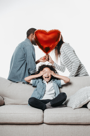 Laughing kid sitting and covering eyes with palms while mother and father hiding their kiss with air balloon. Isolated on background